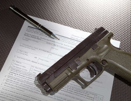 background check: Handgun and paperwork required for a federal background check Stock Photo