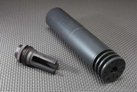suppressor: Suppressor and the mount that allows it to stay on a rifle barrel Stock Photo