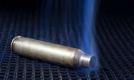 grate: Rifle brass on a black grate that is smoking hot