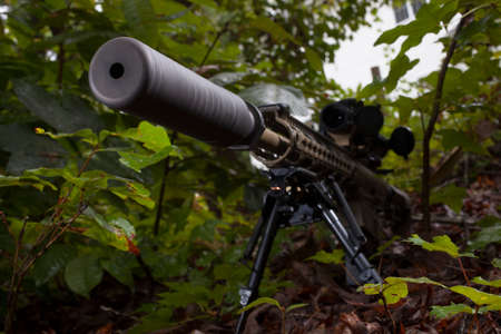 Silencer on a rifle seen from the front in some trees