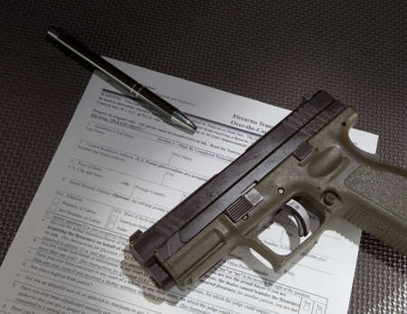 background check: Form to check the background of a gun purchaser and handgun Stock Photo