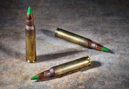 tipped: Rifle cartridges with green tipped bullets on a rock background Stock Photo