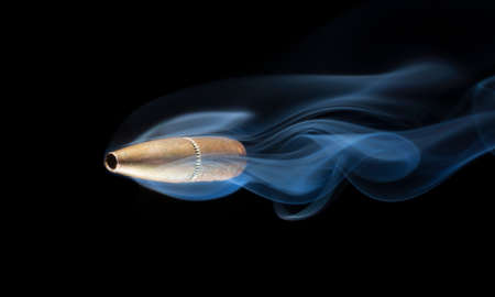 Bronze colored bullet with smoke behind on a black background