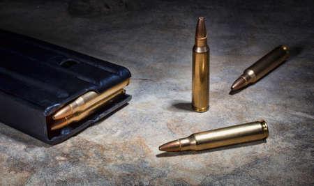 semi automatic: Ammunition and magazine for a semi automatic rifle on a rock Stock Photo