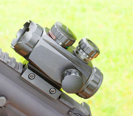 Short rifle scope mounted on a gun with a green background Banco de Imagens