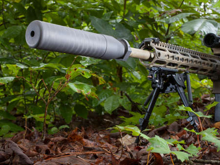 Suppressor on a semi automatic rifle in the forest