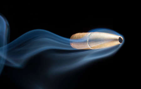Bullet with a copper jacket that has smoke behind on a black background