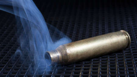 metal grate: Empty rifle ammunition with smoke on a metal grate