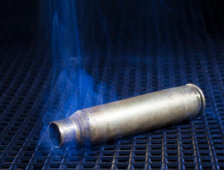 the casing: Empty rifle casing on a black grate with smoke around