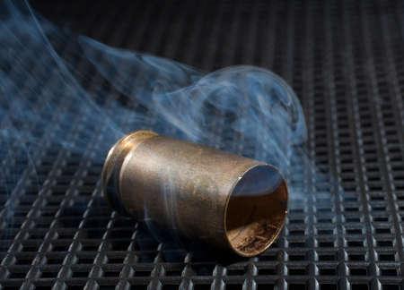 Empty handgun ammunition with smoke on a grate