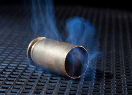 grate: Brass from a handgun with smoke on a black grate Stock Photo