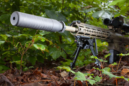Grey suppressor on the end of a semi automatic rifle in the forest