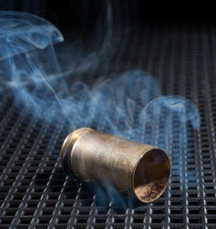 grate: Smoke surrounding an empty handgun casing on a black grate