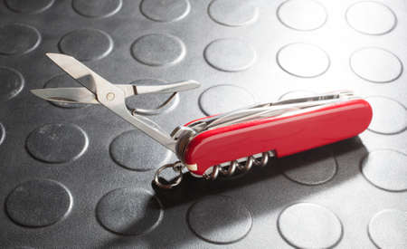 pocket knife: Scissors out on a red pocket knife with a lot of tools