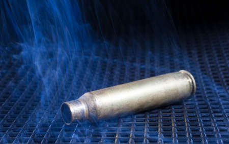 the casing: Empty rifle casing on a black grate surrounded by smoke Stock Photo