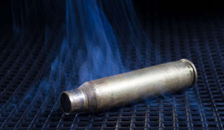 the casing: Smoke rising from a rifle casing on a black grate