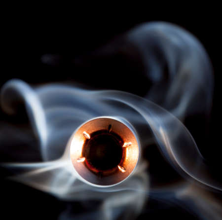 Hollow point bullet with copper coating and smoke coming at the viewer Stock fotó