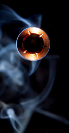 Copper plated hollow point bullet and smoke coming at the camera