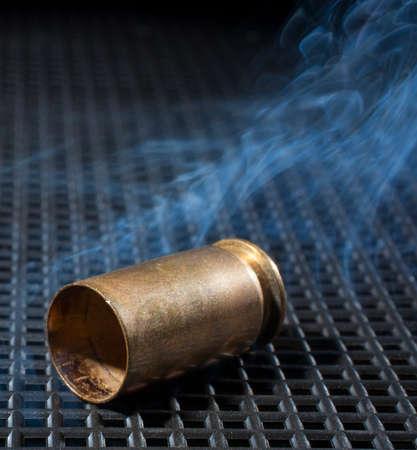 semi automatic: Brass from a semi automatic pistol with smoke around Stock Photo