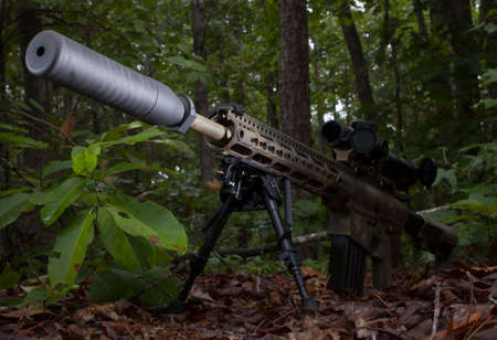 the silencer: Modern sporting rifle with a silencer in a bunch of trees
