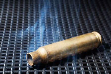 the casing: Rifle casing that is empty and has smoke all around Stock Photo