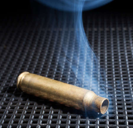 grate: Empty rifle brass on a black grate with smoke around