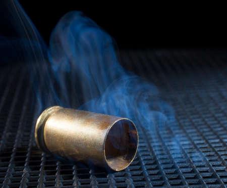 grate: Handgun brass on a black grate smoking after being shot Stock Photo