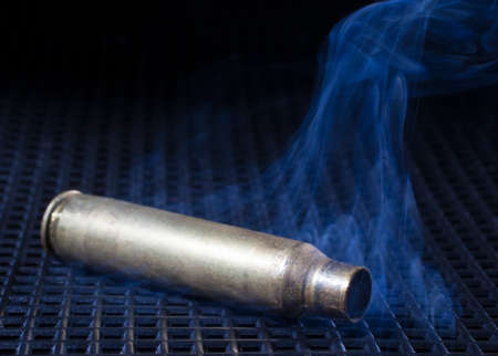 grate: Empty rifle brass on a black grate that is smoking Stock Photo