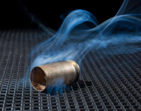 Handgun brass after being fired with smoke nearby Stok Fotoğraf