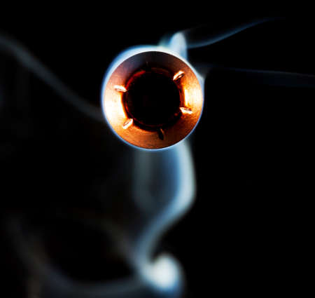 hollow: Hollow pointed bullet with smoke behind on a black background Stock Photo