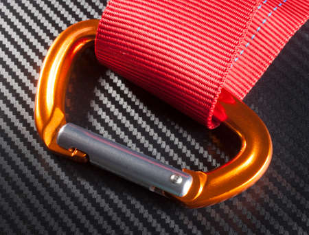 carabiner: Orange carabiner with red nylon on a graphite background