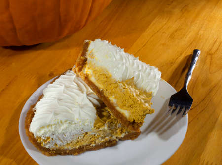Two slices of whipped pumpkin pie on a white plate