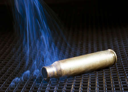 grate: Rifle brass on a black grate with blue smoke rising