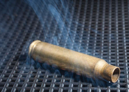 the casing: Rifle casing that is still hot and surrounded by smoke