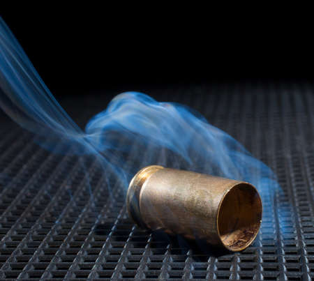 the casing: Empty handgun casing on a black grate with smoke