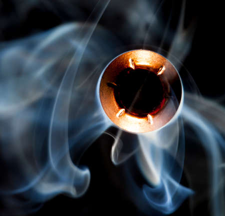 hollow: Smoke surrounding a hollow point bullet on a black background Stock Photo
