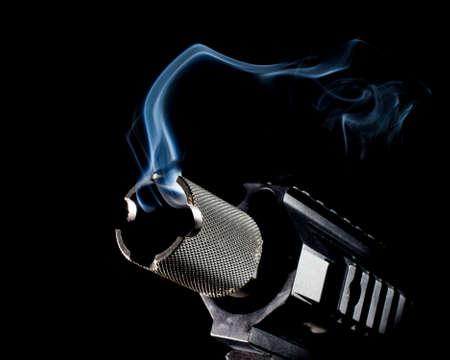 semi automatic: Modern semi automatic gun that has smoke coming from the barrel