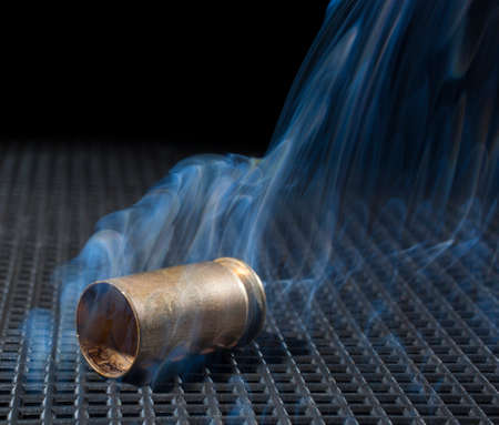 grate: Empty handgun shell on a black grate with smoke nearby