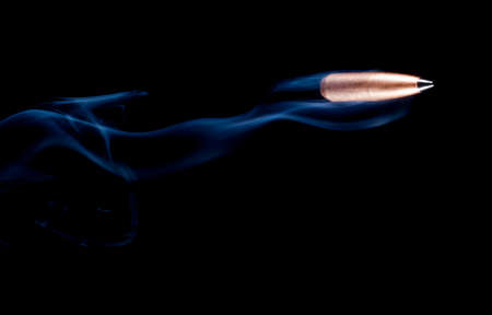 plating: Bullet with copper plating and a polymer tip that looks like it is flying with smoke behind Stock Photo
