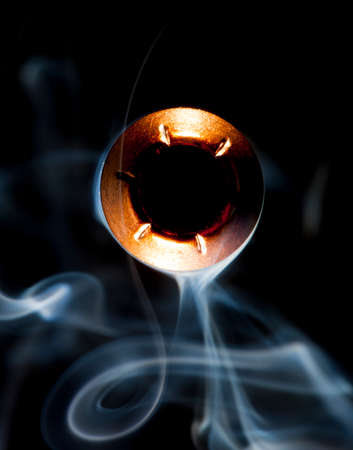 Hollow point bullet pointed at the camera with smoke around Stock fotó