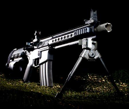 netting: AR-15 style handgun on green netting with a dark background Stock Photo
