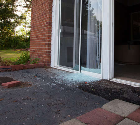 Shattered sliding glass window the morning after a home invasion Foto de archivo