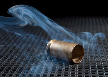 grate: Empty brass from a handgun on a black grate with smoke Stock Photo