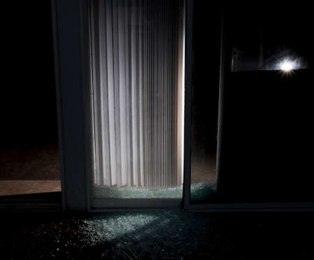 shattered glass: Shattered glass door on a house with a flashlight inside at night