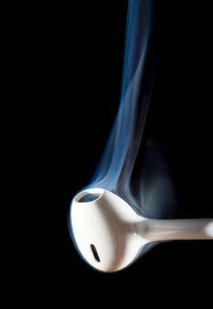 ear buds: One earphone on a black background with smoke rising