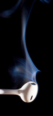 ear buds: Smoke rising from a pair of white ear buds on a black background Stock Photo