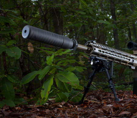 suppressor: Suppressor on a rifle that is in a bunch of trees