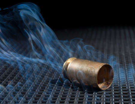 the casing: Handgun casing after a shot with smoke rising next to it