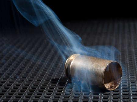 grate: Empty handgun hull on a black grate and smoke rising