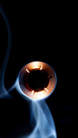 bullet camera: Copper colored hollow point bullet and smoke pointed at the camera Stock Photo
